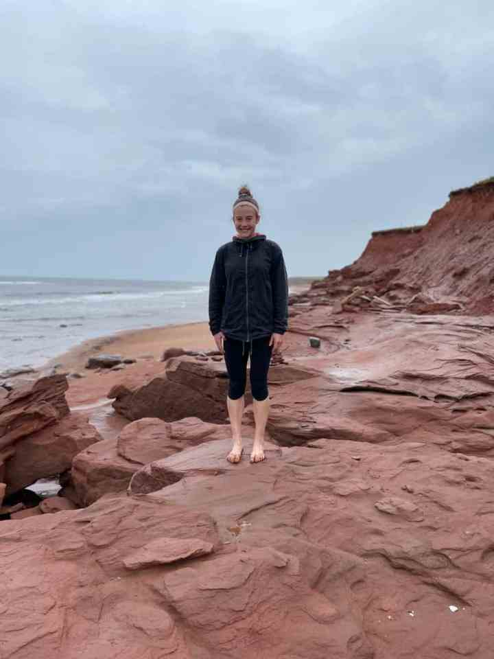 Allison standing on the red rocks at Thunder Cove beach