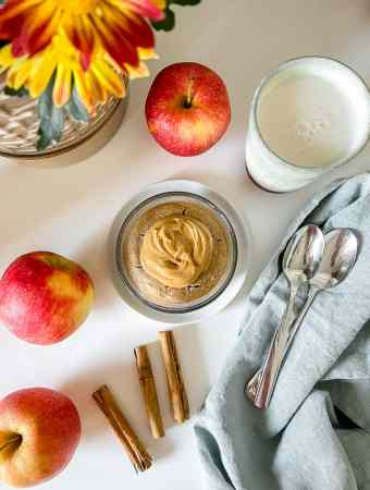 overhead photo of the apple spice blended baked oats in a dish surrounded by a few apples, cinnamon sticks, a glass of almond milk, and a plant