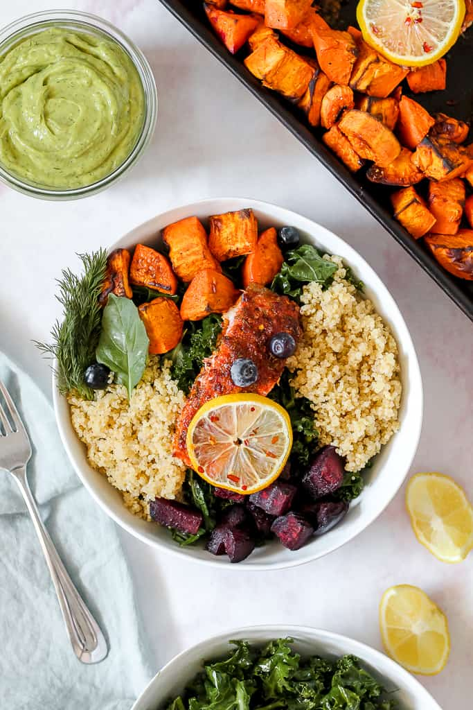 overhead photo of a bowl of the sheet pan lemon paprika salmon filet on top of a bowl of quinoa, roasted sweet potato, beets, and kale.