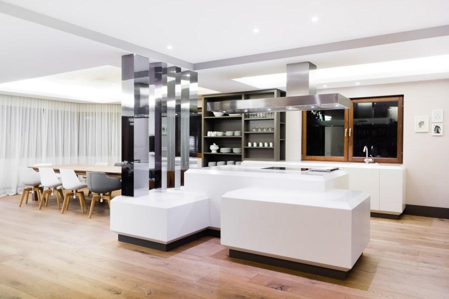 modernes Penthouse mit weißer Küche und Spiegelsaeulen