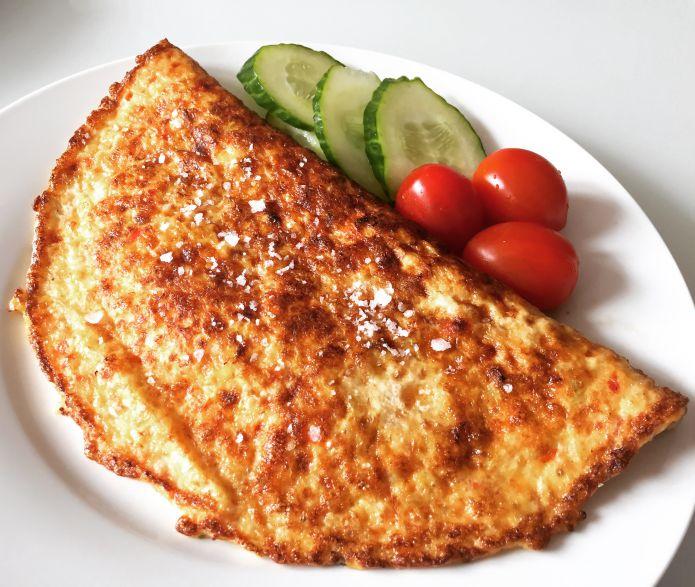 Oste-omelet med løg og peberfrugt dertil tomater og agurk