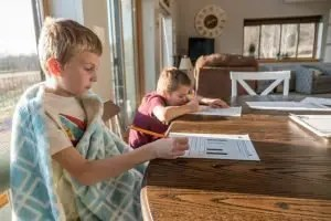 two boys sitting at the table writing on a piece of paper