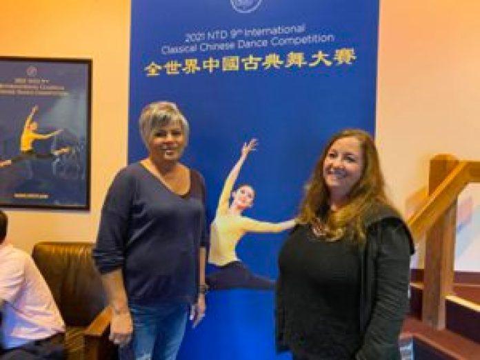 Suger Loaf艺术中心管理人员戴斯乐(左)和同事在大赛海报前合影,她盛赞新唐人电视台恢复传统文化的努力。(施萍/大纪元)