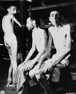 Three emaciated survivors in a barracks in the...