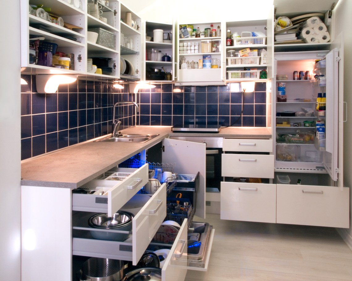 White kitchen with cabinet doors and drawers opened or removed so that real life stuff can be seen in cabinets Kitchen Solutions For Small Spaces