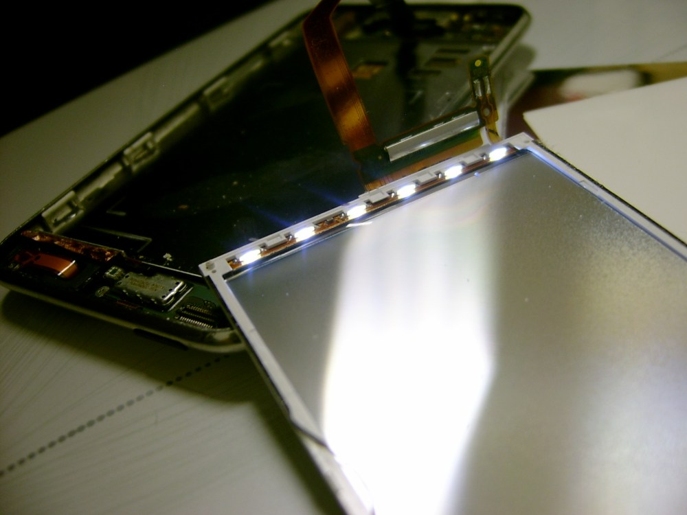 medium resolution of an apple ipod touch music player disassembled to show the array of white edge led s powered on with the device rethecat
