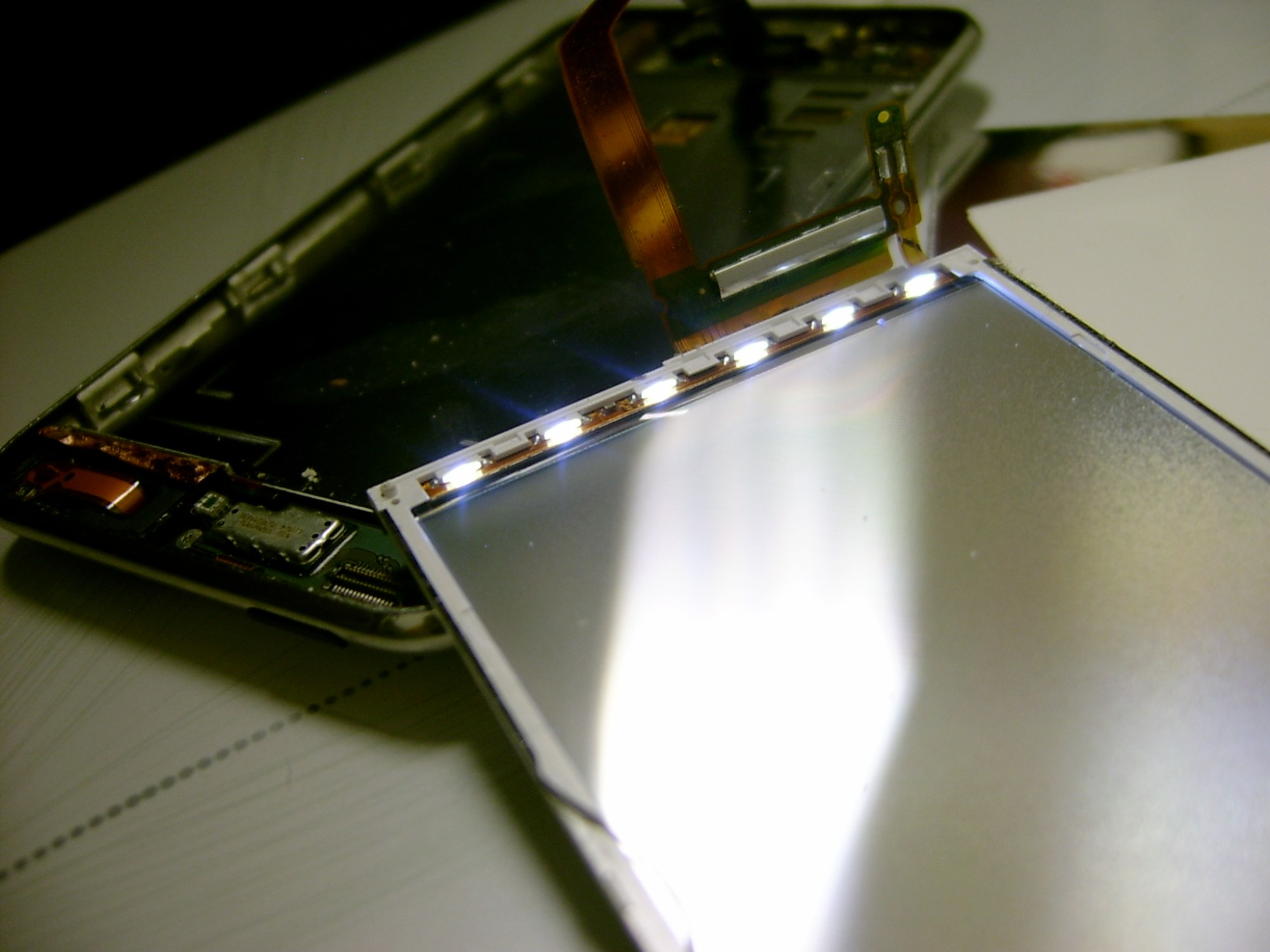 hight resolution of an apple ipod touch music player disassembled to show the array of white edge led s powered on with the device rethecat