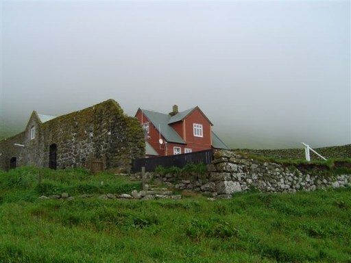 Red farmhouse against a grey sky