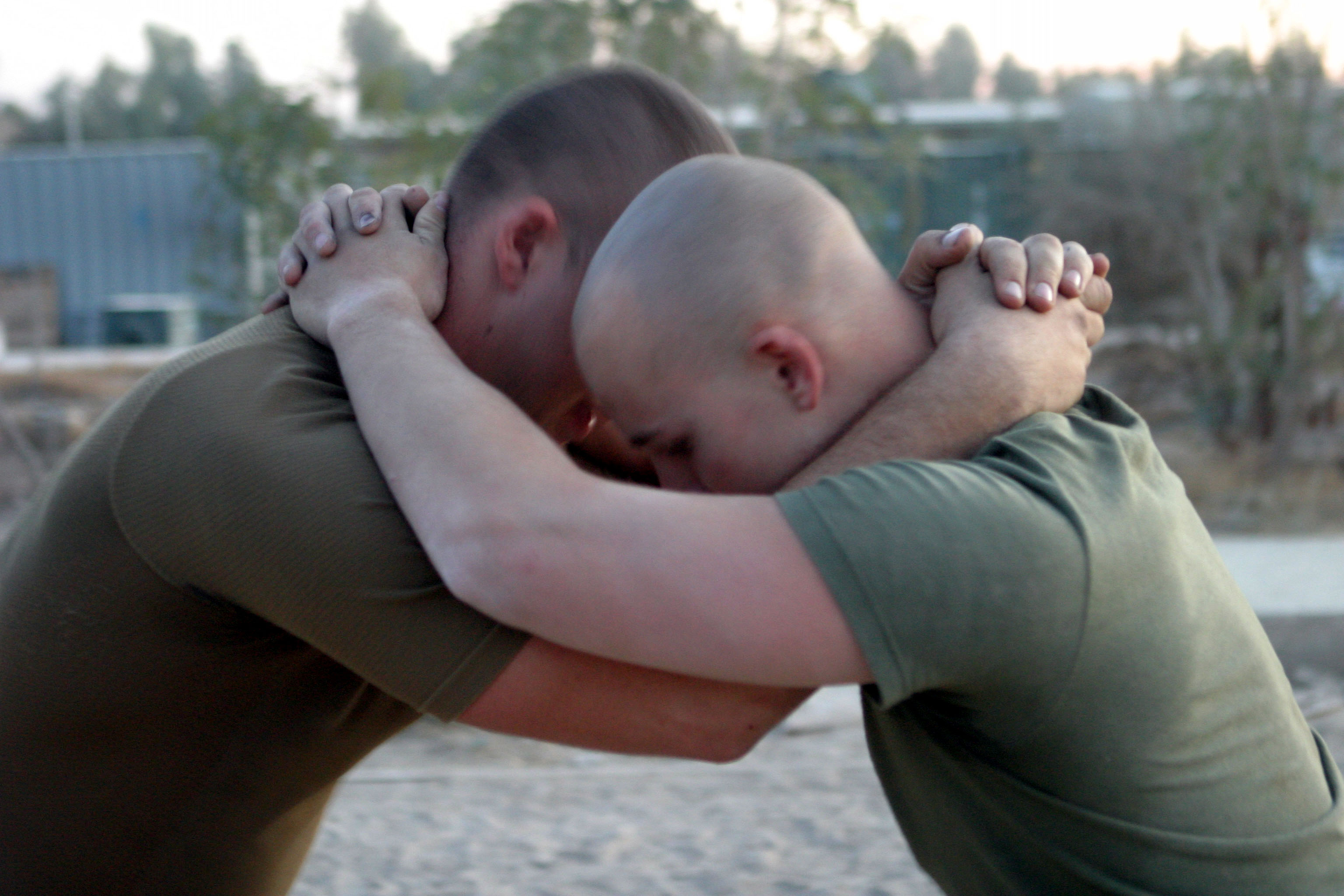 Two men in khaki T-shirts have wrapped their arms around each other's neck