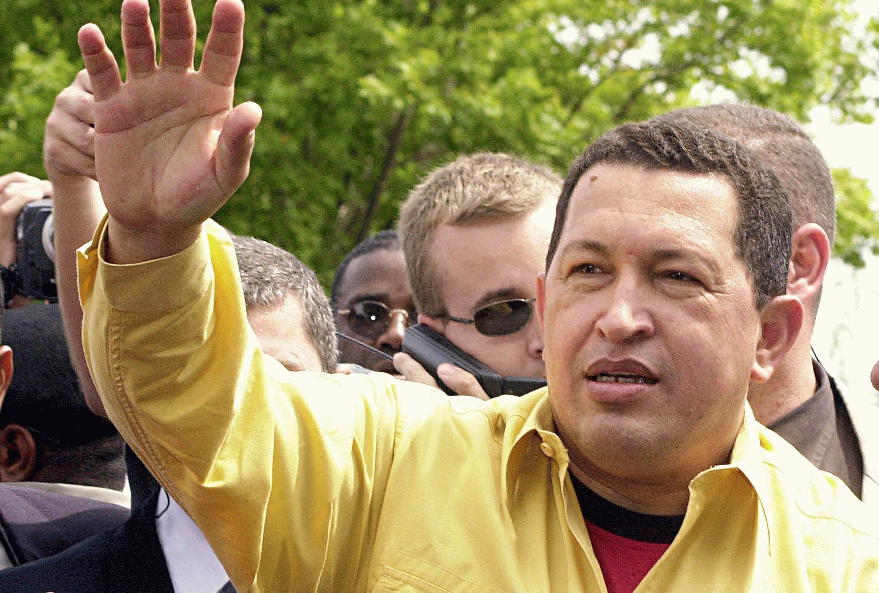 Hugo Chávez, de camisa amarela, saudando a multidão, com vários seguranças