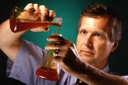 English: A chemist with Erlenmeyer flasks