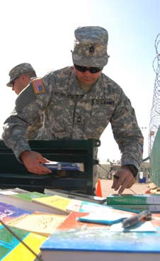 English: A Joint Task Force Guantanamo Trooper displays reading materials from the JTF library for detainees to choose from. The library holds 8000 books and magazines in English, Pashtu and Arabic. ??? JTF Guantanamo photo by Navy Petty Officer 2nd Class Patrick Thompson