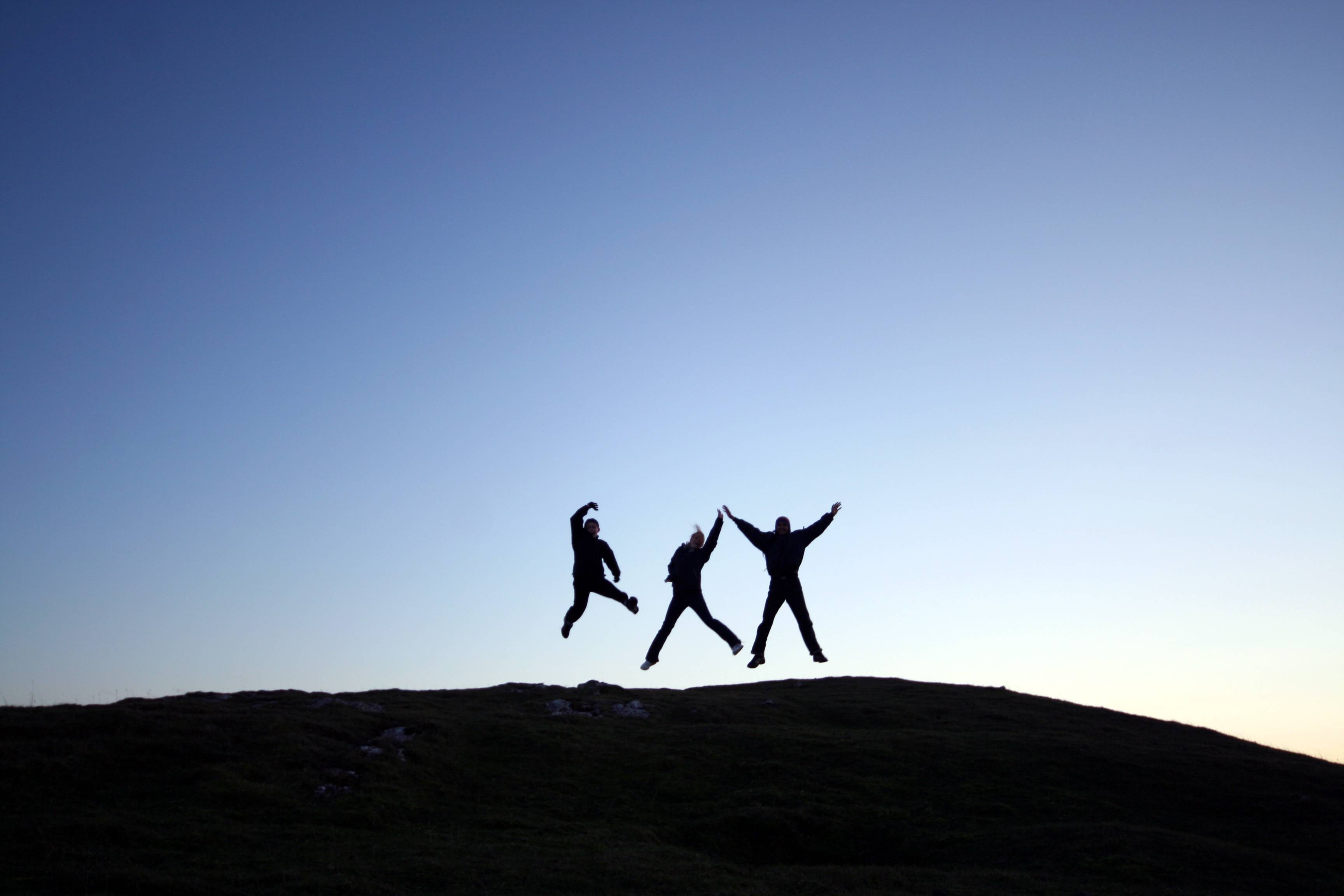 Jumping for joy. Photo of three men jumping on top of Moel Hiraddug by Cat via Wikimedia Commons
