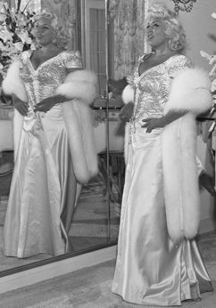 Mae West posing in front of mirror for promotion