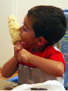 Niño comiendo mazorca de elote en un palo