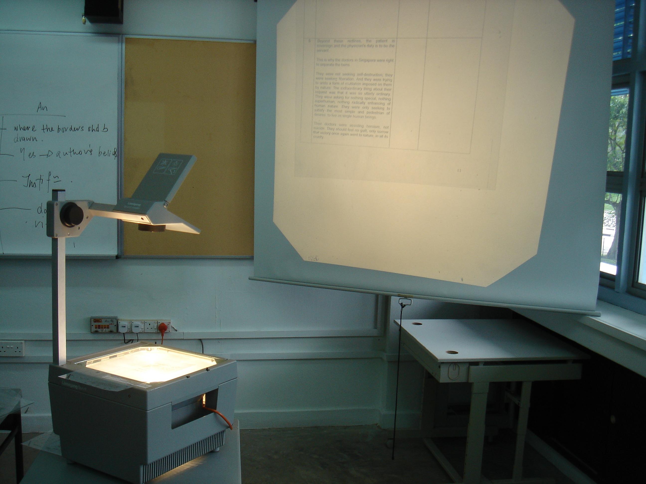 Overhead projector -- projects light through a transparent sheet with pictures, text, through a lense and onto a flat surface such as a wall.