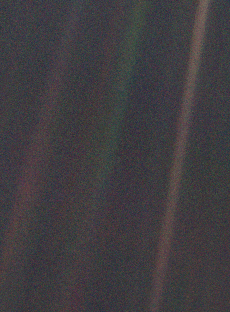 Seen from about 6 billion kilometers (3.7 billion miles), Earth appears as a tiny dot (the blueish-white speck approximately halfway down the brown band to the right) within the darkness of deep space.