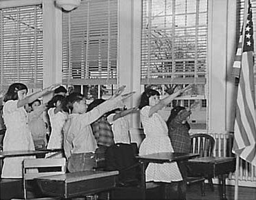 Students in an unnamed school in 1941, offering the Bellamy Salute for the Pledge of Allegiance.