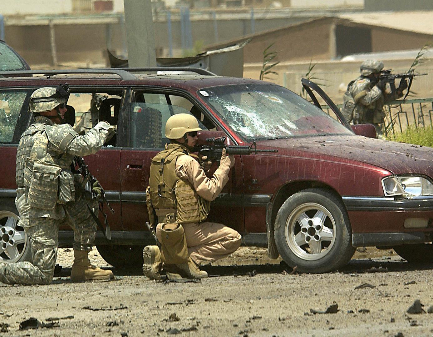 US troops take cover from small arms fire while investigating a car bomb explosion in Tameem, Ramadi, August 10, 2006