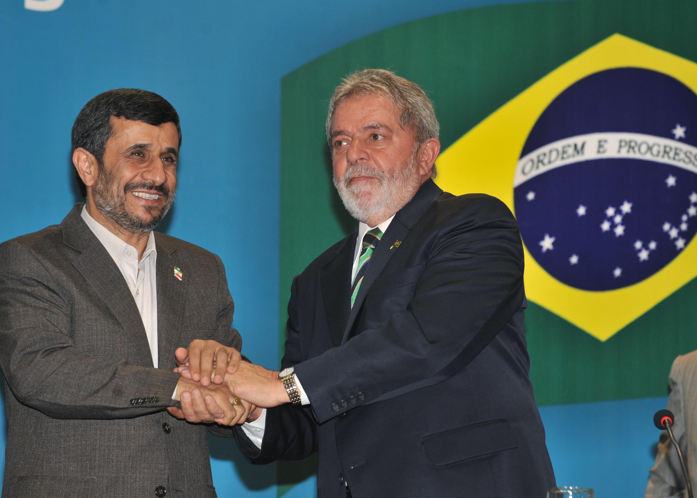 Homem de barba grisalha e cabelos negros (Ahmadinejad) usando paletó cinza com broche na forma da bandeira do Irã e camisa branca, sem gravata, aperta a mão de homem (Lula) com paletó azul-marinho e gravata listrada de azul-marinho e verde, com broche da bandeira do Brasil, à frente de parede azul com uma bandeira brasileria pendurada