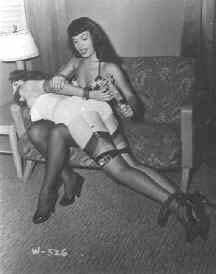 English: Bettie Page spanking a tied-up woman