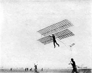 Photographie en noir et blanc d'un homme qui s'envole accroché à un planeur biplan.