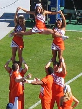 English: Collegiate cheerleaders perform a hig...