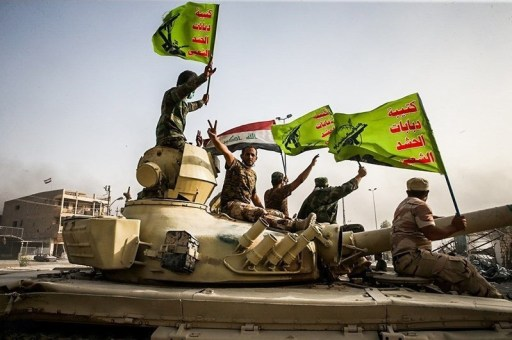Raising flag of Iraq and Popular Mobilization Forces after defeating DAESH