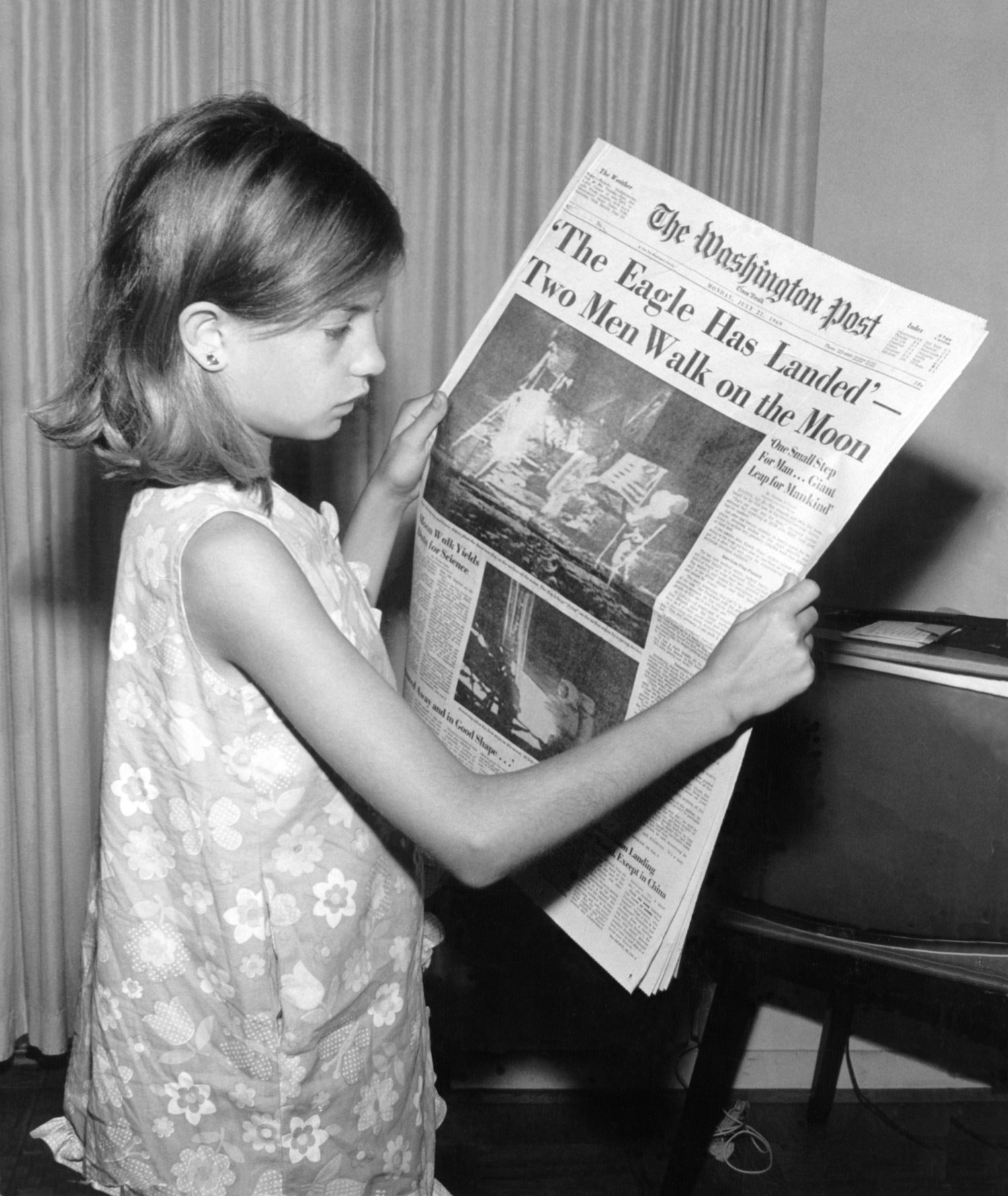 A girl holds The Washington Post of Monday, Ju...
