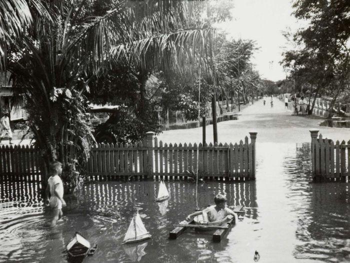 COLLECTIE TROPENMUSEUM De broers Henk en Hans Japing spelen in de tijdens hoog water ondergelopen tuin van het huis met nummer 34 op de Boekit Ketjil in Palembang TMnr 60051055 Mainan Bocah Belanda VS Mainan Bocah Pribumi