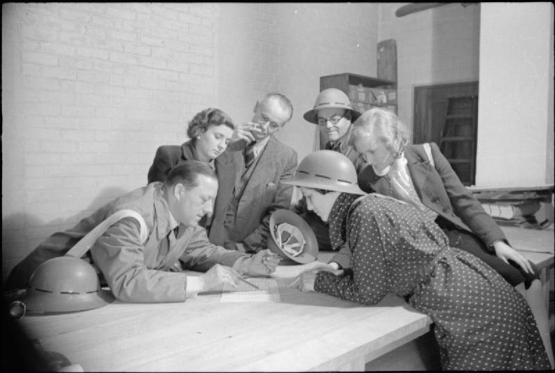 A vintage photo of three men and three women gathered around a table, looking at a piece of paper. They wear civilian clothes and carry firefighter helmets.