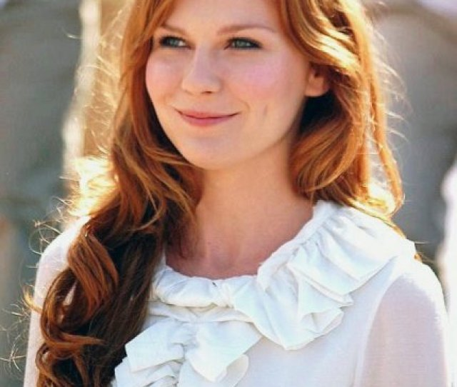 A Red Headed Woman Smiles While Wearing A White Top With Frill Detailing