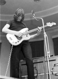 A monochrome image of Roger Waters playing bass guitar. He has shoulder-length hair, black attire, and is standing in front of a microphone.