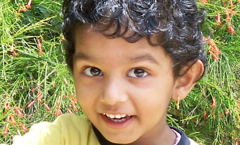 English: A cherubic happy Indian child