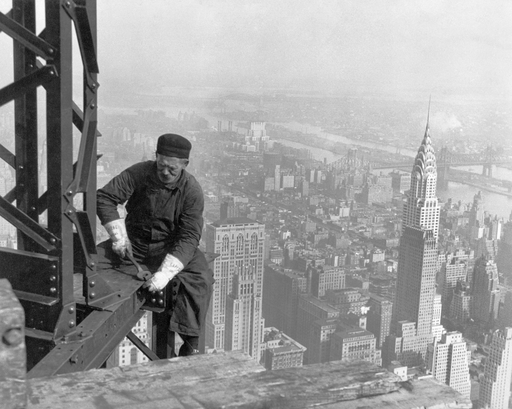 hight resolution of a worker bolts beams during construction the chrysler building can be seen in the background