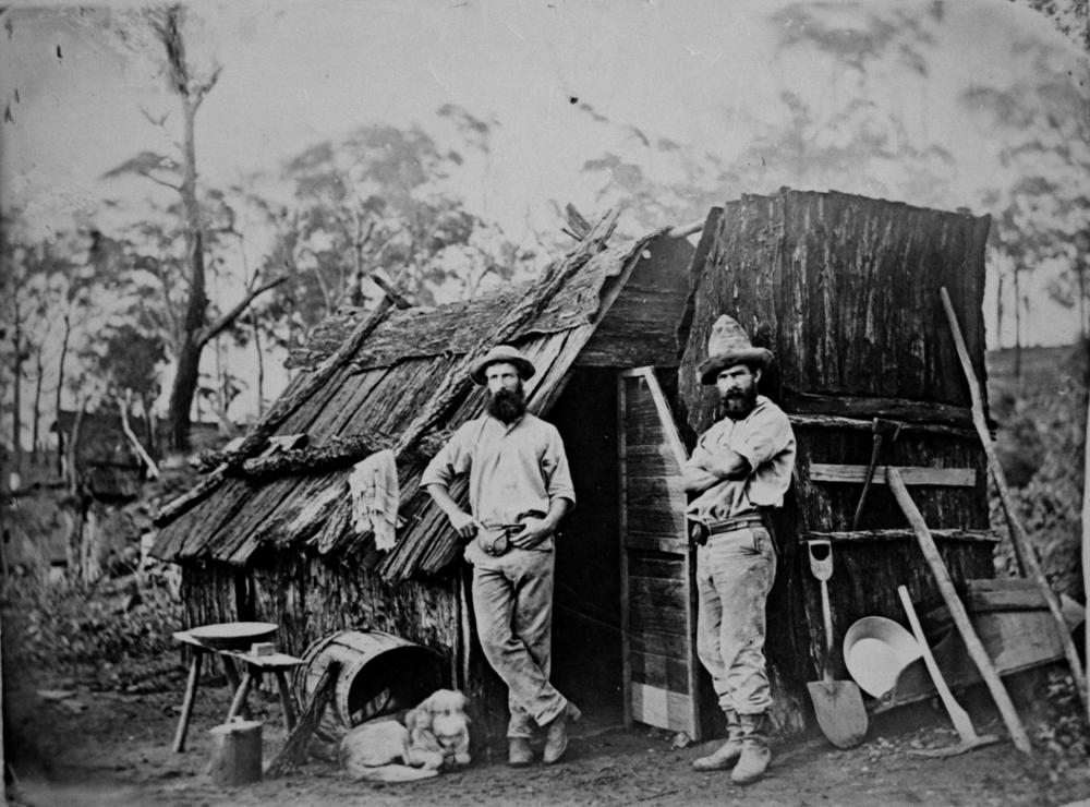 Two men with beards and hats stand in front of a bark hut.