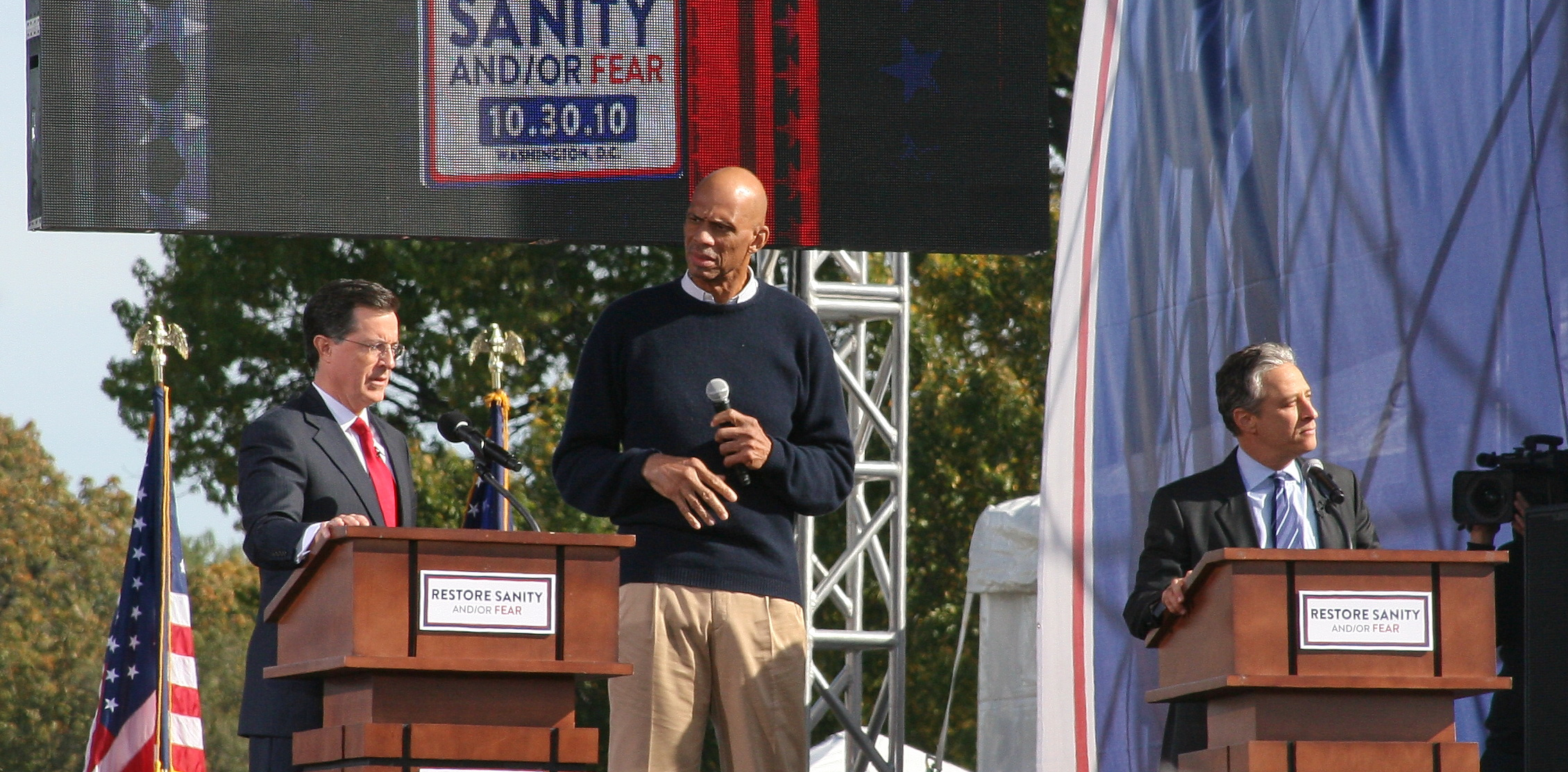 Kareem Abdul-Jabbar (center), Stephen Colbert to the left and Jon Stewart to the right.
