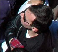 A photo of a white man wearing black sunglasses and a black leather jacket, with his right hand wrapped in a red handkerchief.