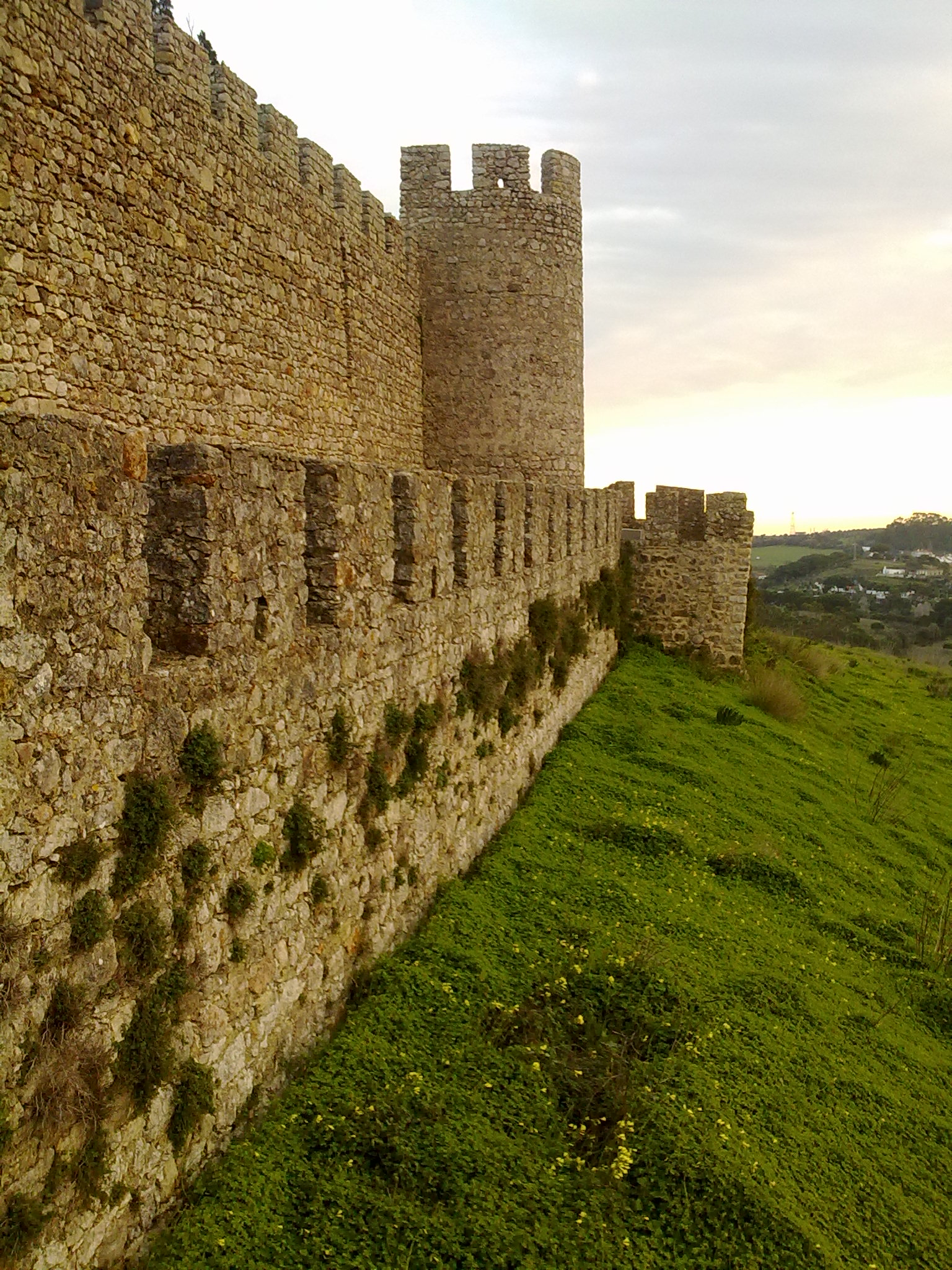 Castelo de Santiago do Cacém - muralha, torre e barbacã (By Adriao. Creative Commons via Wikimedia Commons).