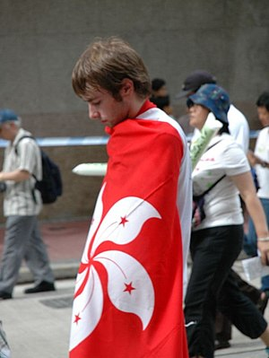 Marcher wrapped in a flag of Hong Kong at a pr...