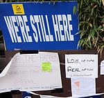 """Signs reading """"We're still here"""", """"Love, not hate / Real, not fake"""" and other messages"""