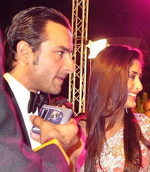 A man and woman facing to the left. The man has black hair and sharp features, while wearing a tuxedo. Somebody is holding a tape recorder in front of his mouth. The woman wears a white sari and has flowing brown hair. She is smiling.
