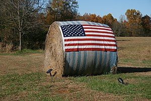 English: A round bale of hay with a flag of th...