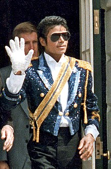 A mid-twenties African American man wearing a sequined military jacket and dark sunglasses. He is walking while waving his right hand, which is adorned with a white glove. His left hand is bare.