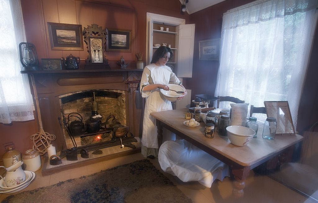 FileWoman batting a mix in a 19th century kitchen