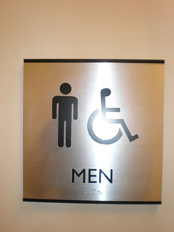 A metal male restroom sign in an office buildi...