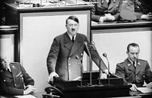 Picture of a man in a suit with a mustache who looks like Hitler speaking behind a microphone.