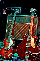 Two electric guitars, a light brown violin-shaped bass and a darker brown guitar, rest against a Vox amplifier.