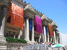 Facade of imposing building with Greek columns. Large colored banners hang from the building's top. A crowd of people is in front.