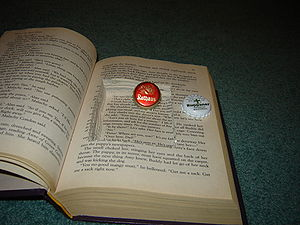 A hollowed out book, with bottle caps for scale.